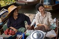 Laughing market_woman holding a dish, another watching her, Floating Market, Damnoen Saduak, near Bangkok, Ratchaburi, Thailand
