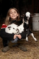 Girl in the barn laughing with her baby goat