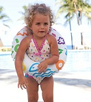 Toddler girl in swimsuit and inner tube