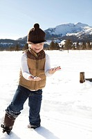 Young boy holding snow
