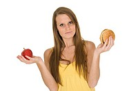 Caucasian woman holding an apple and hambuger trying to decide which one to eat