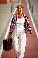 White, blue and red stripes dressed mature woman walking down the red carpet