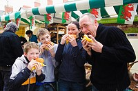 A family eating freshly cooked organic wild boar burgers, Aberystwyth Farners Market, Wales UK