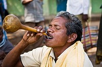 A Bonda man drinking Todi in the weekly Onkadeli market in orissa, India.
