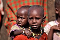 A young Masai girl carries a child on her back in the Masai Mara region of Kenya.
