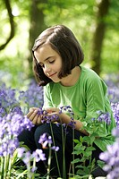 England, Buckinghamshire, Stokenchurch, Young girl sitting in a wood full of Bluebells.