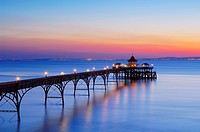 England, North Somerset, Clevedon, Sunset over the pier in the Bristol Channel at Clevedon. In 1913, the timber landing stage of the pier, which had d...