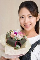 Woman holding bouquet and smiling at the camera