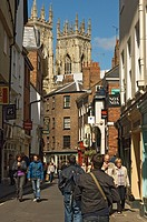 England, North Yorkshire, York, Visitors and shoppers in Low Petergate, a traffic free street full of shops and restaurants leading to York Minster.