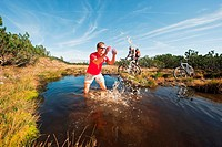 Austria, Salzburger Land, Bikers by lake, man splashing water