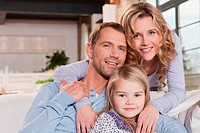 Germany, Cologne, Family sitting on sofa, smiling, portrait, close-up (thumbnail)