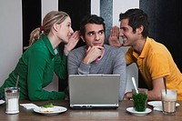 Friends using laptop, whispering