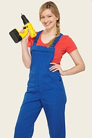 Young woman holding power drill, smiling, portrait
