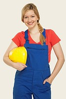 Young woman holding hard hat, smiling, portrait