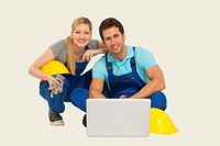 Man and woman in overall using laptop, smiling, portrait