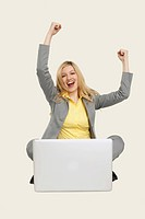 Businesswoman with laptop, clenching fist