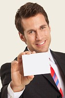 Businessman holding blank note, smiling