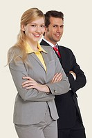 Businesswomen and men smiling, arms crossed