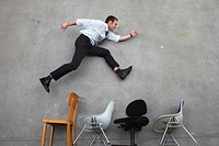 Businessman jumping over chairs, side view, elevated view
