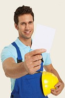 Man in overall holding blank paper and hardhat, smiling, close_up
