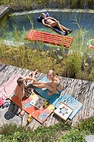 Austria, Salzburger Land, Teenagers 14_15 relaxing at garden pool, elevated view