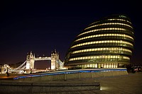 England, London, South Bank, City Hall at night with Tower Bridge in the distance.