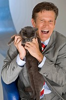 Businessman holding cat, laughing, portrait