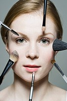 A woman with various make_up brushes applying make_up to her face