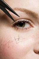 Scissors cutting hair on a woman, detailed shot of eye