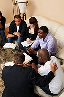 a group of adults praying together with their bibles open
