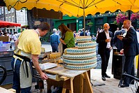 England, London, Borough, A market trader selling Cheese from the round in Borough Market.