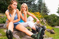 Two women at a park wearing inline skates