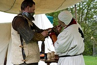 England, Essex, Castle Hedingham, A knight being prepared for battle at a medieval re_enactment at Hedingham Castle.