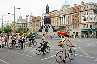 Dublin City  Statue of Daniel O'Connell and cyclists waiting to cross O'Connell Street, the city centre main thoroughfare