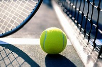 Tennis ball and net on court near tennis racket and shadows
