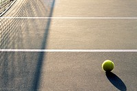Tennis ball on court and net with shadows
