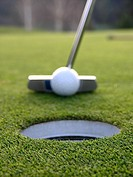 Close-up of putter about to hit ball into hole on putting green