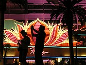 Silhouettes of tourists on the Las Vegas Strip in front of the neon Flamingo Casino sign
