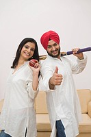Sikh couple with cricket bat and a ball
