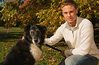 Young man in a park with a dog