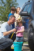 a family washing a vehicle