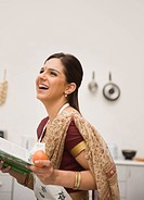 Woman holding a recipe book in the kitchen and smiling