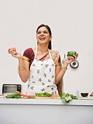 Woman holding vegetables in a kitchen and smiling