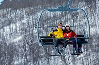 Couple on ski hill riding chairlift