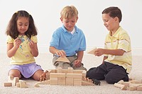 three children building noah´s ark with wooden blocks