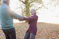 Senior couple holding hands outdoors in autumn