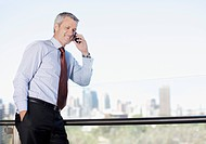 Businessman talking on cell phone on balcony