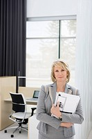 Businesswoman holding paperwork in office
