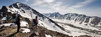 A backcountry snowboarder and skier enjoy the view from the west ridgeline of Powerline Pass near Anchorage, Alaska