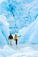 Young couple walking amongst icebergs frozen in Portage Lake at Portage Glacier, Chugach National Forest, Southcentral Alaska